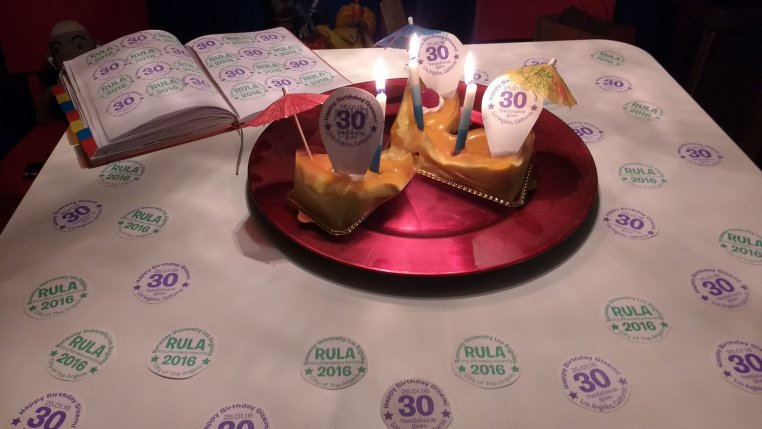"3 slices of dessert on a table. The table is decorated with logos for ""RULA"" and for ""Gizem's 30th Birthday"""