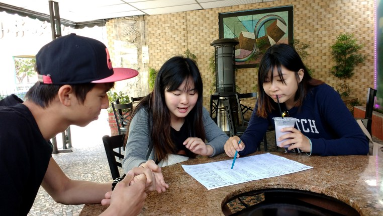 3 people sitting at a table and looking at a menu at Hot Pot City in New Taipei, CA