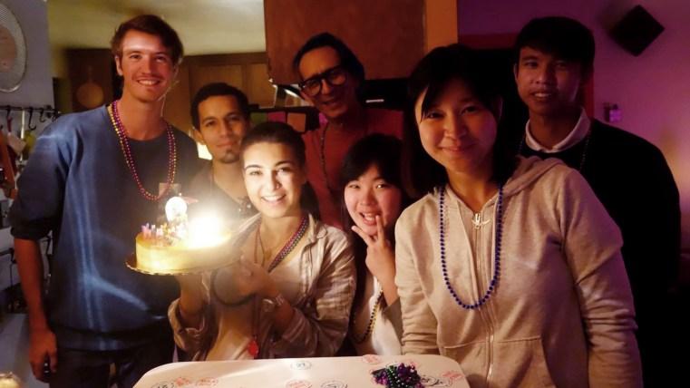 gathering around Marta Troya's 21st birthday cake in the Runaway University cafateria