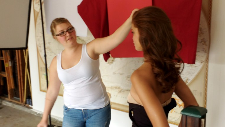Tamara makes a fine adjustment on Carmen's hair