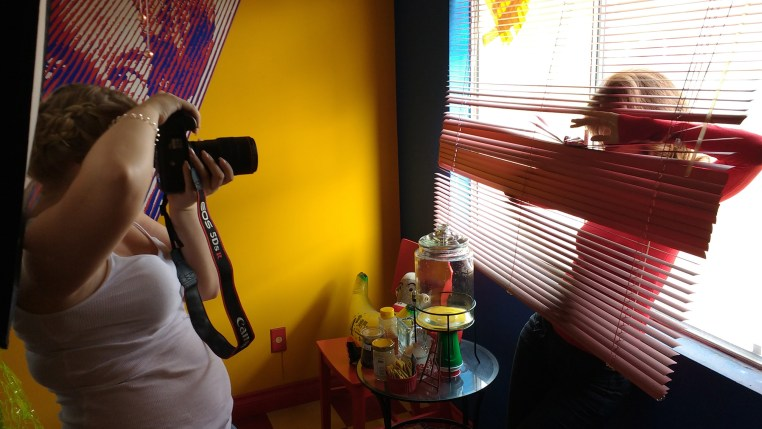 Tamara Williams photographing Carmen Lee Solomons through red window blinds