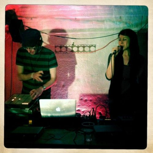Alice with a microphone and another musician with a laptop