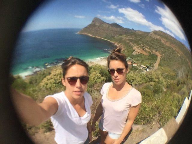 Elise & Lana taking a wide-angle selfie on a coastal cliff