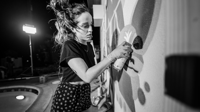 "Merijein Saperas painting a graffiti writing mural of the letters ""RULA"" at Runaway University in Los Angeles, California."
