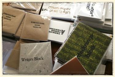 Skrivblock med boktryckta omslag och inlaga av restpapper från tryckeriet – inpackade och klara för försäljning.