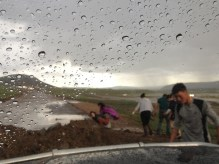 locals help dig dirt in a failed attempt to get their van on the move