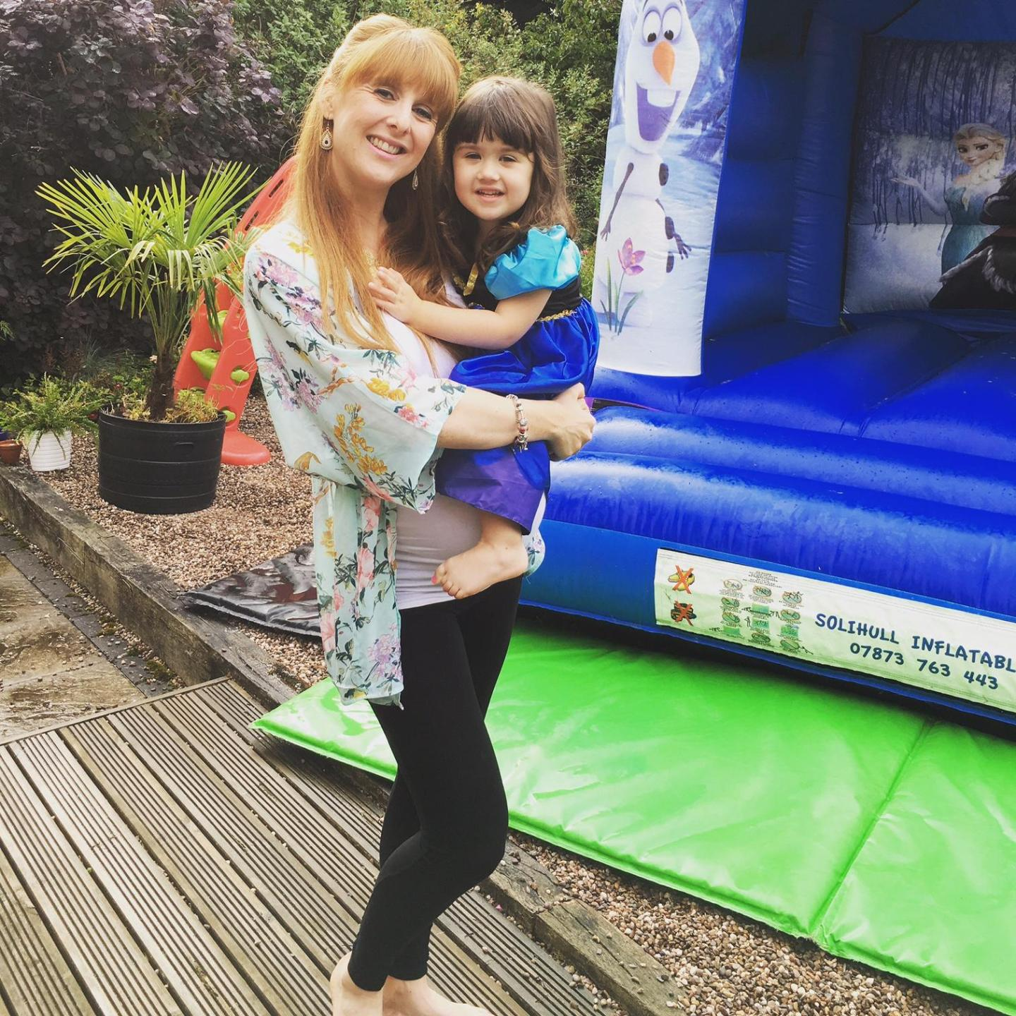 mum and daughter in front of a bouncy castle