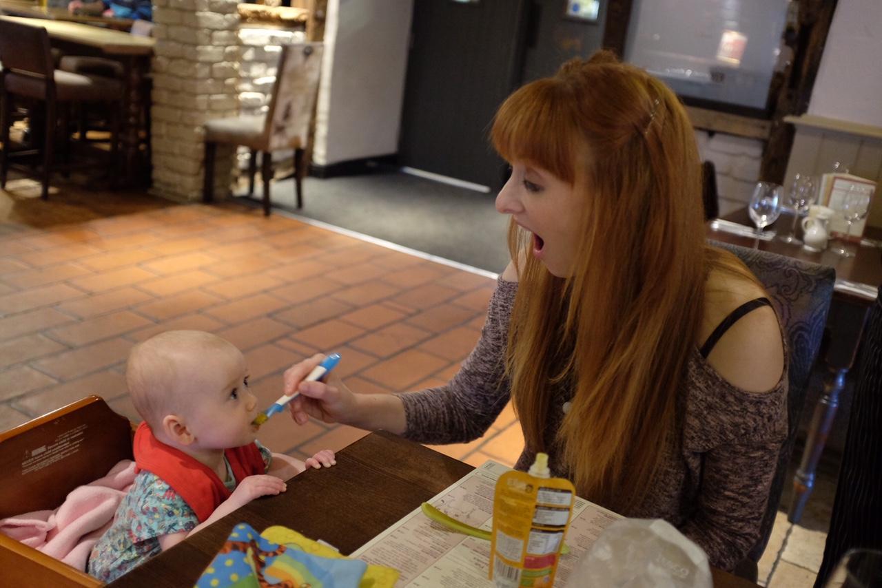 Baby girl being fed Ella's Kitchen pouch