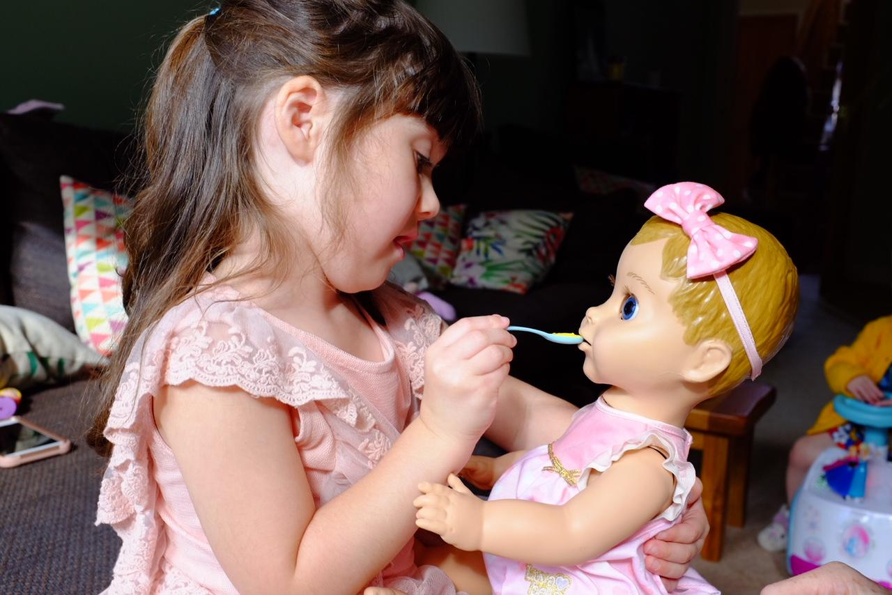 Girl feeding Luvabella doll with spoon