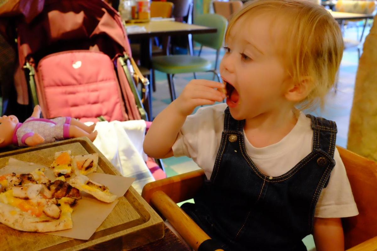 2 year old eating chicken and cheese flatbread from Turtle Bay