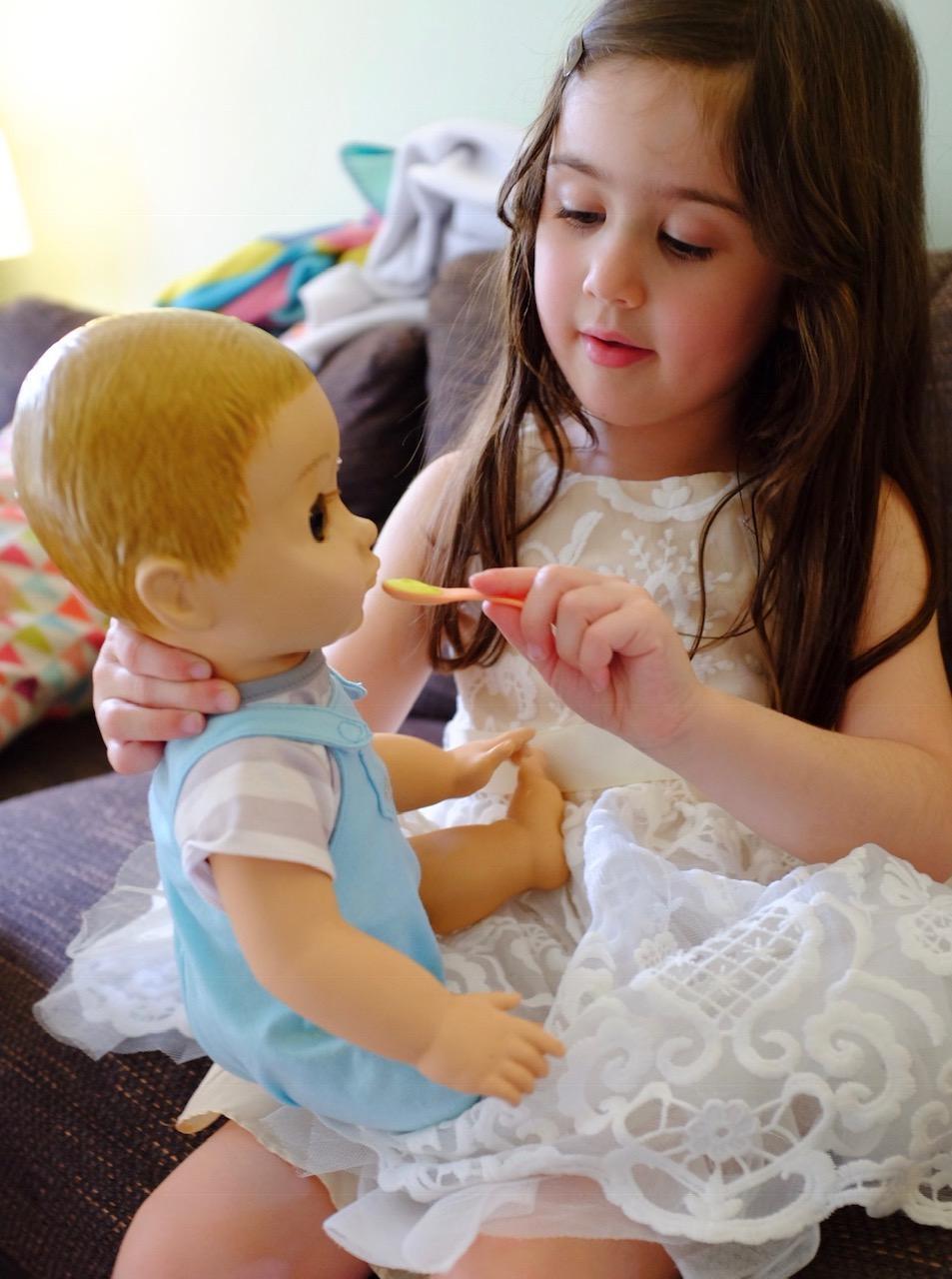 girl feeding doll