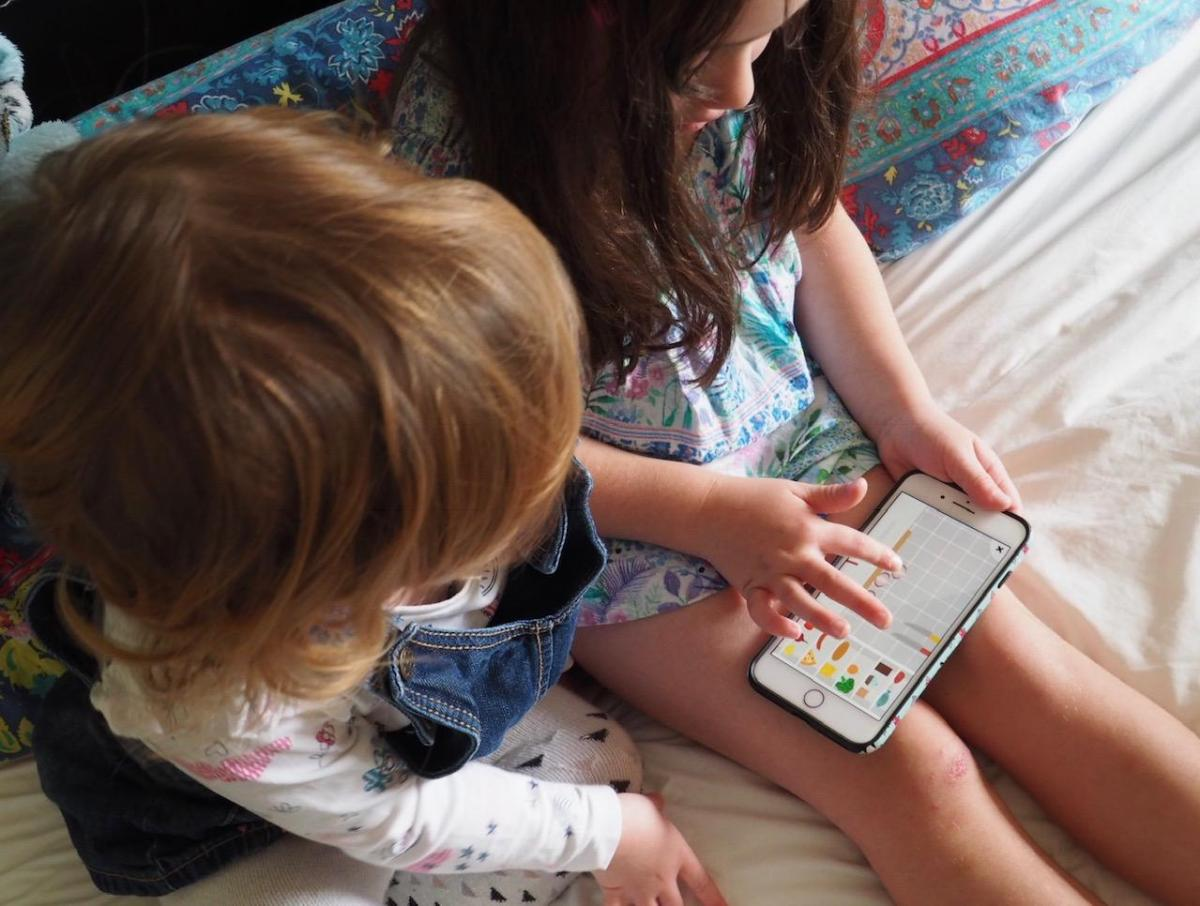 two girls playing The Fitoons App