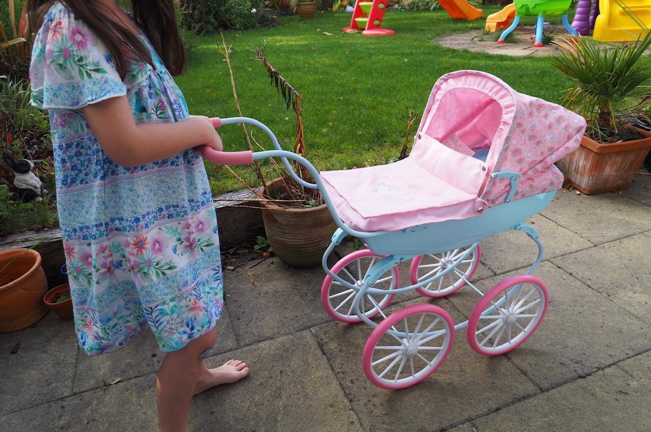 girl pushing the baby annabell carriage pram