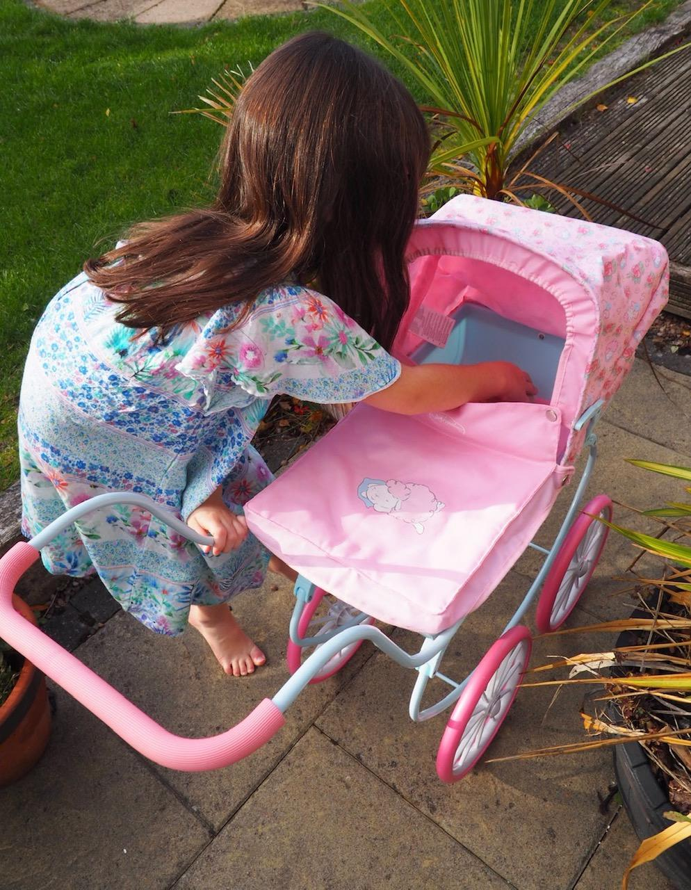 girl comforting her baby - Baby Annabell carriage pram