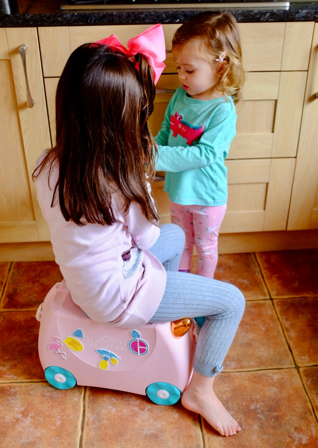 sisters playing with Flossi the Flamingo Trunki