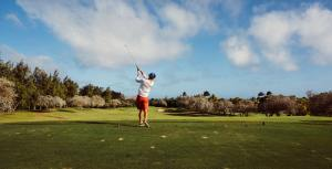 A golfer hits the golf ball across a scenic, green landscape.
