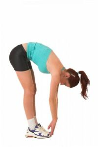 Young woman completing a hamstring stretch.