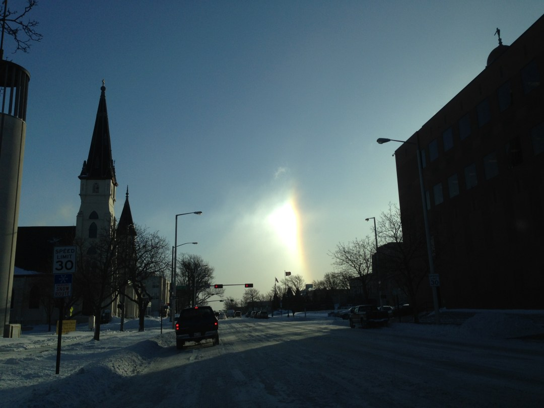 Rainbow or Sun Dog? Notice the solar glory between St. Mary's Catholic Church on the left at the Nebraska State Capitol on the right.