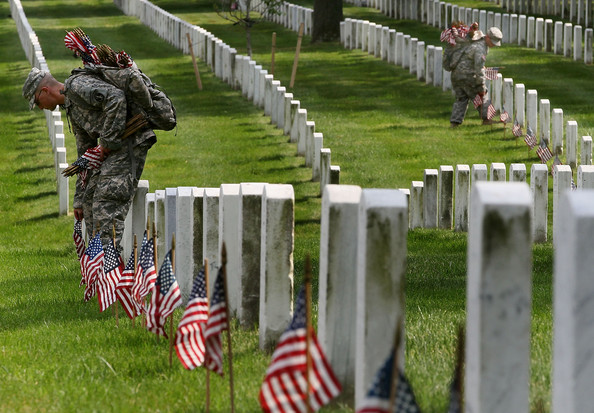 National Guardsmen placing flags at graves at Arlington National Cemetery for Memorial Day.