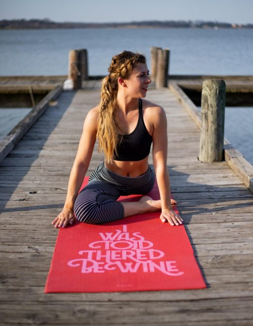 19 Reasons to Workout Today Even if You'd Rather Not | Running in Heels blog | Kasey sits in pigeon pose on a dock at the lake wearing a black sports bra from Fabletics and striped leggings from Lululemon.