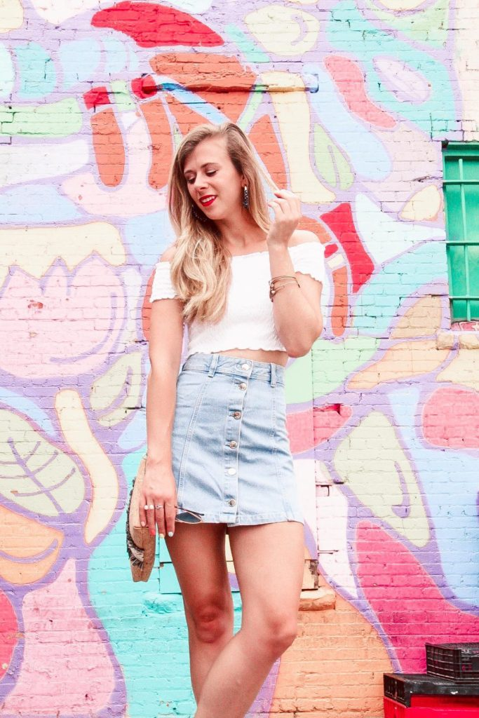Murals of Dallas | Blonde Girls stands in front of whimsical print mural wearing white crop top and denim mini skirt