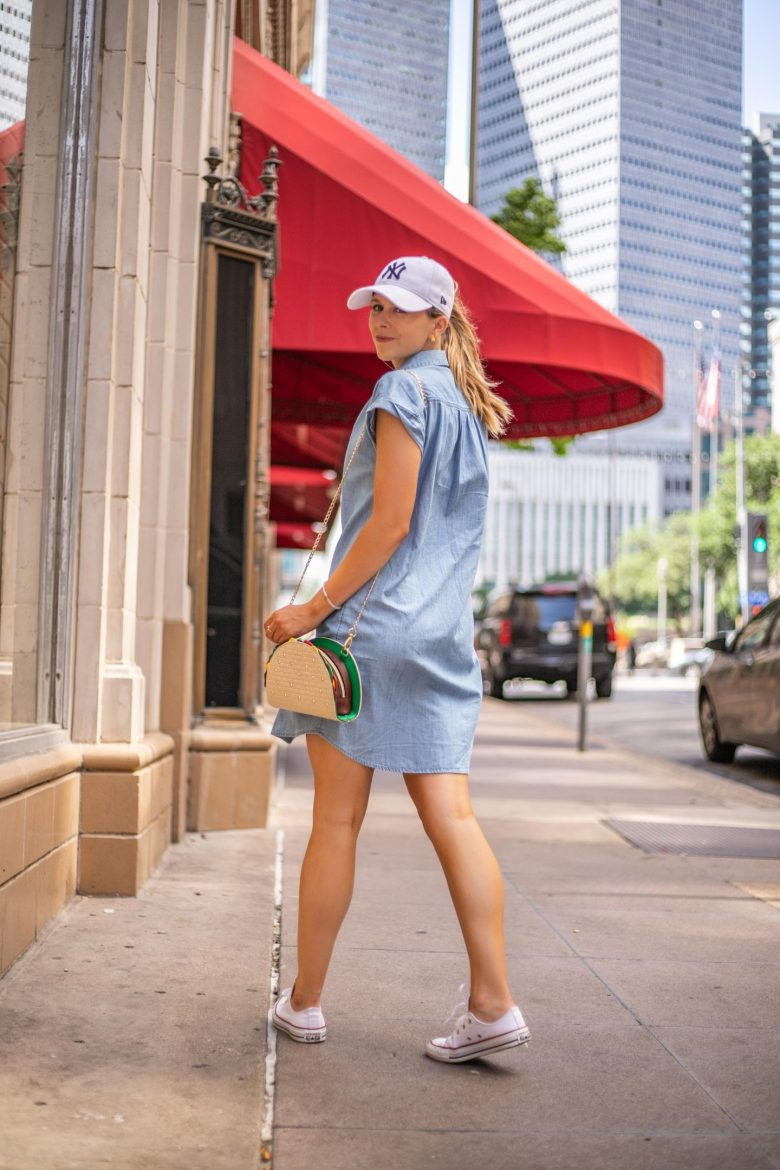 How to Style a Chambray Shirtdress, styling tips featured by top US fashion blog, Running in Heels: image of a woman wearing an Old Navy chambray shirtdress, New York Yankees baseball cap, Red Dress Boutique taco purse, and BAUBLEBAR Gummi bear statement earrings