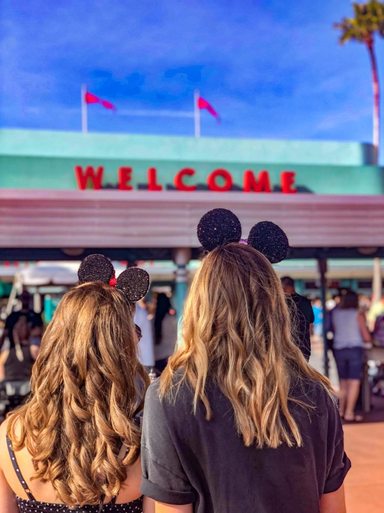 Adult Guide to Disney World Theme Parks Broken Down by Park | Running in Heels | Welcome to Hollyeood Studios Park in Disney World, two blondes look at the entrance wearing minnie mouse ears.