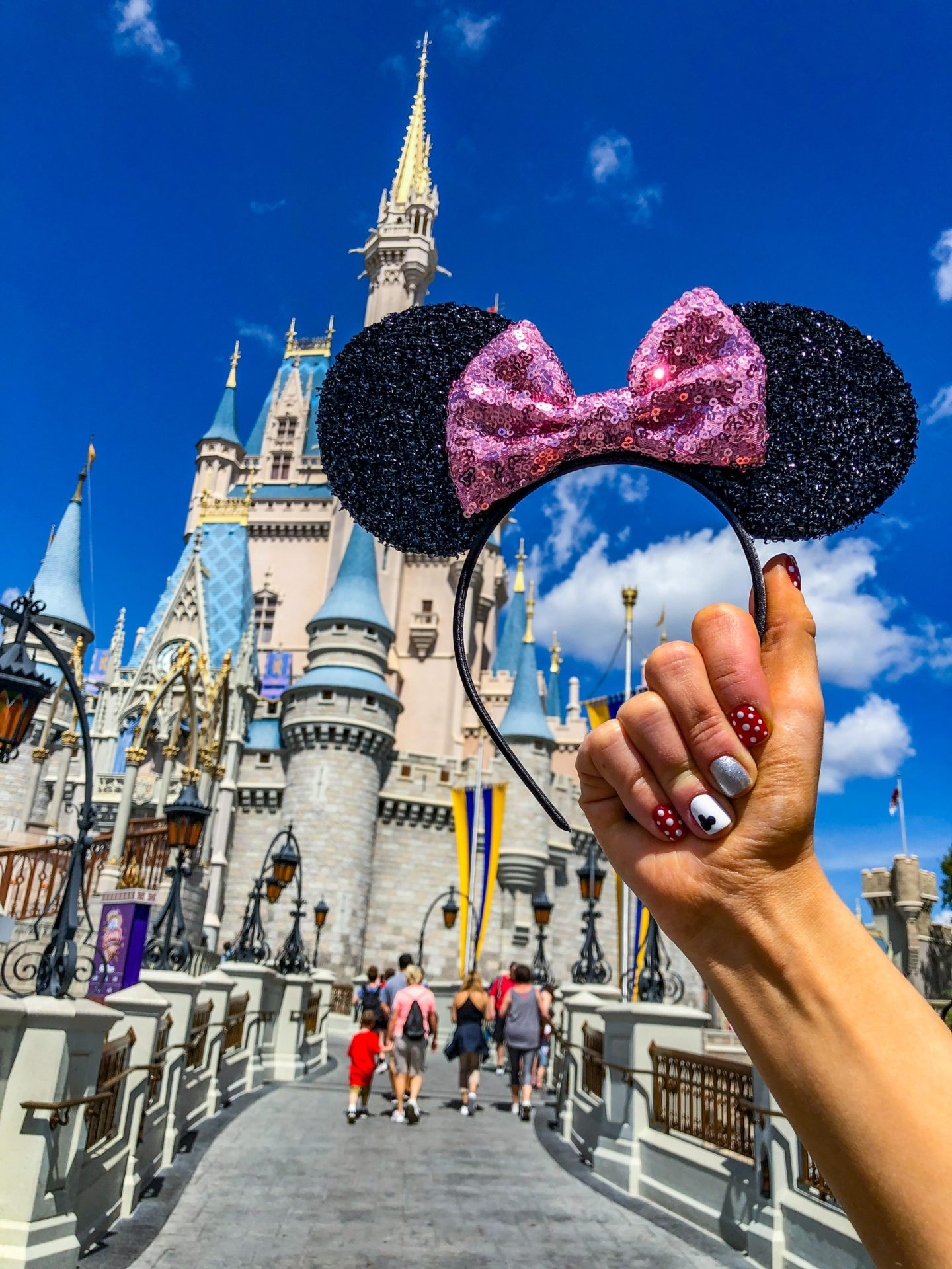 Adult Guide to Disney World Theme Parks Broken Down by Park | Running in Heels | Two sisters stand in front of the castle in Magic Kingdom holding minnie mouse ears with painted Disney inspired nails.