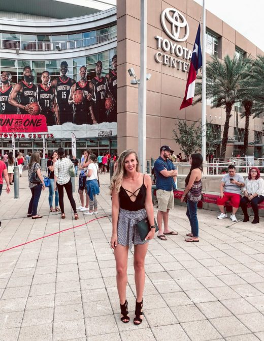 Getting Concert Ready with Palm Beach Tan: Blonde Dallas Blogger standing in front of Toyota Center in Houston wears Versa Pro Spray tan, black strappy bodysuit from Express, Gingham paper bag shorts, and black strappy heels, with a black Kate Spade Clutch
