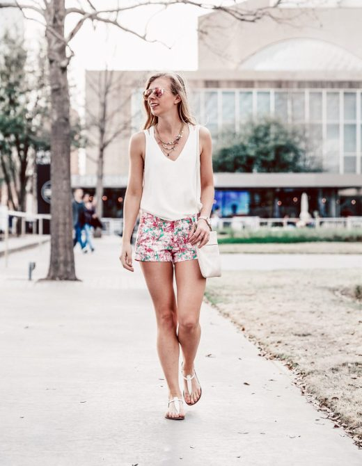Lilly Pulitzer After Party Sale Favorites | Running in Heels | Summer styles | Girl walks down sidewalk wearing Lilly Pulitzer shorts and a white tank top, neutral shoulder The Sak bag, pink Diff Eyewear aviators, and T-strap sandals by Sam Edelman.
