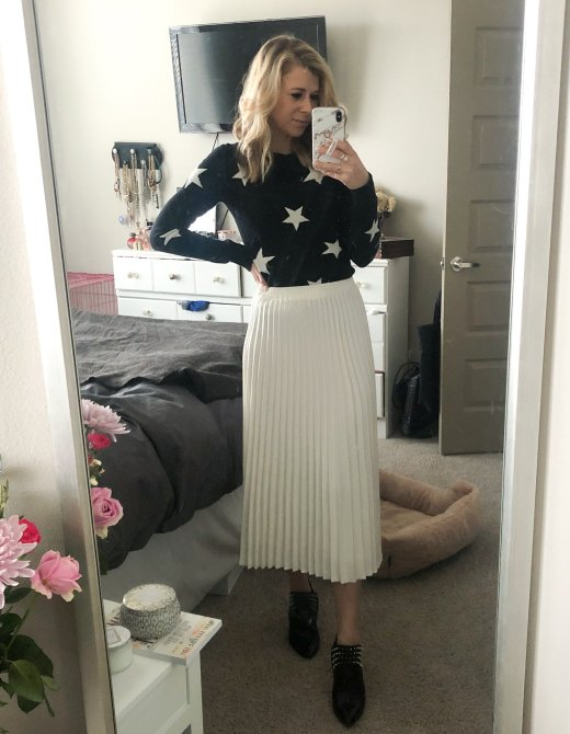 Top US fashion and lifestyle blogger, Running in Heels wears a Star Sweater with white pleated skirt and black leather Sam Edelman booties