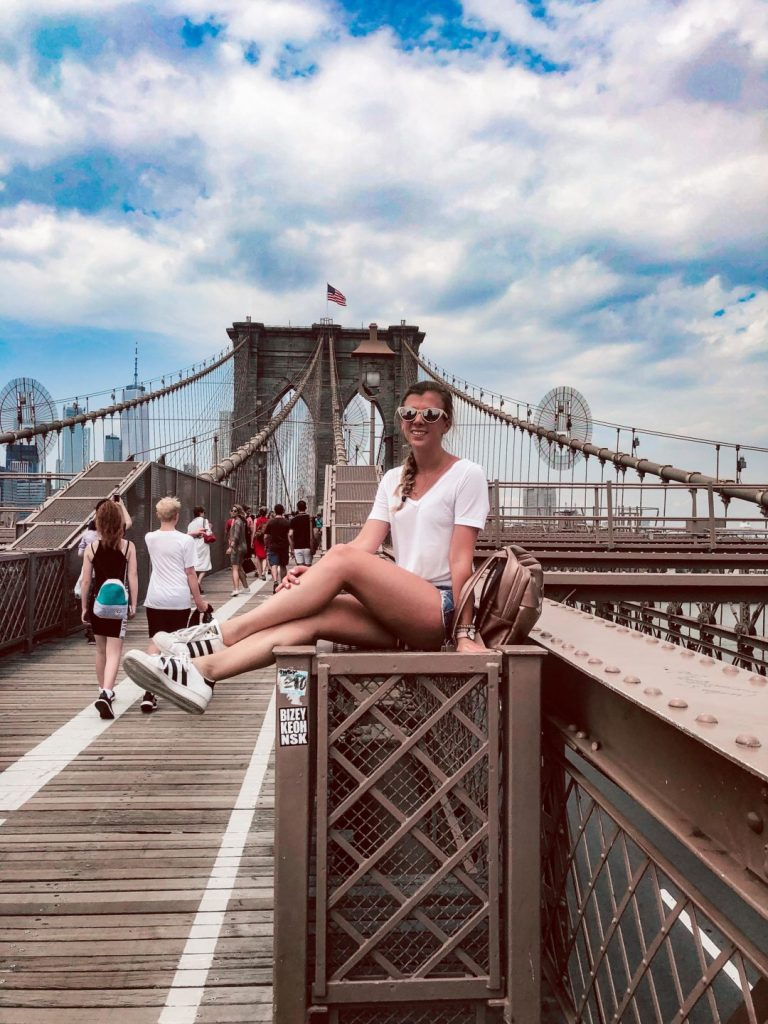 Things to do in NYC in the summer when you've already been there | Girl sits onthe Brooklyn Bridge | What to wear in NYC in the Summer | Summer outfits | Travel outfit