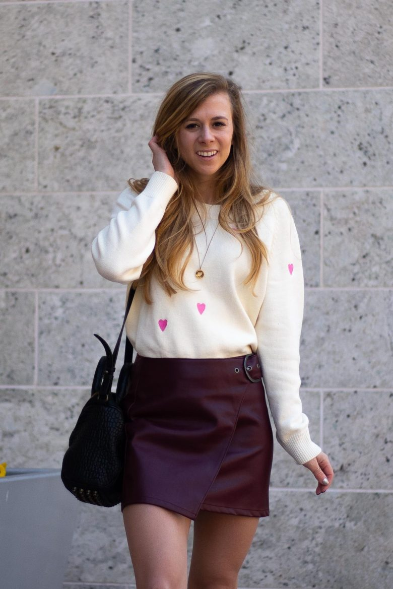 Valentine's Day outfit, cream sweater with pink hearts on it paired with a burgundy faux leather skirt