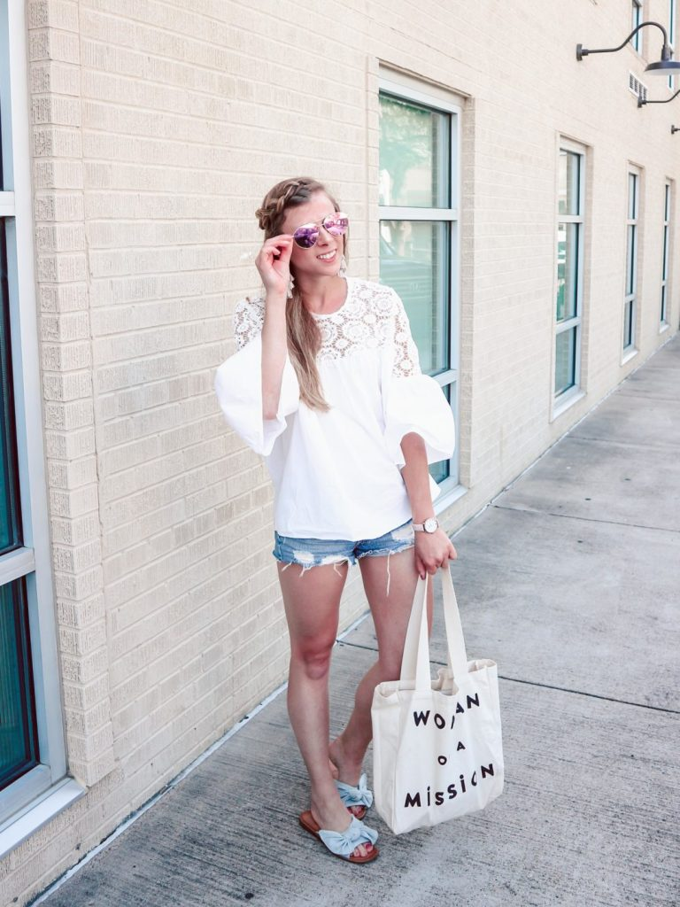 Dallas blogger Running in Heels, blonde wears summer outfit with white crochet top and bell sleeves. Paired with distressed denim shorts, Feed canvas Woman on a Mission bag, and white t-strap sandals