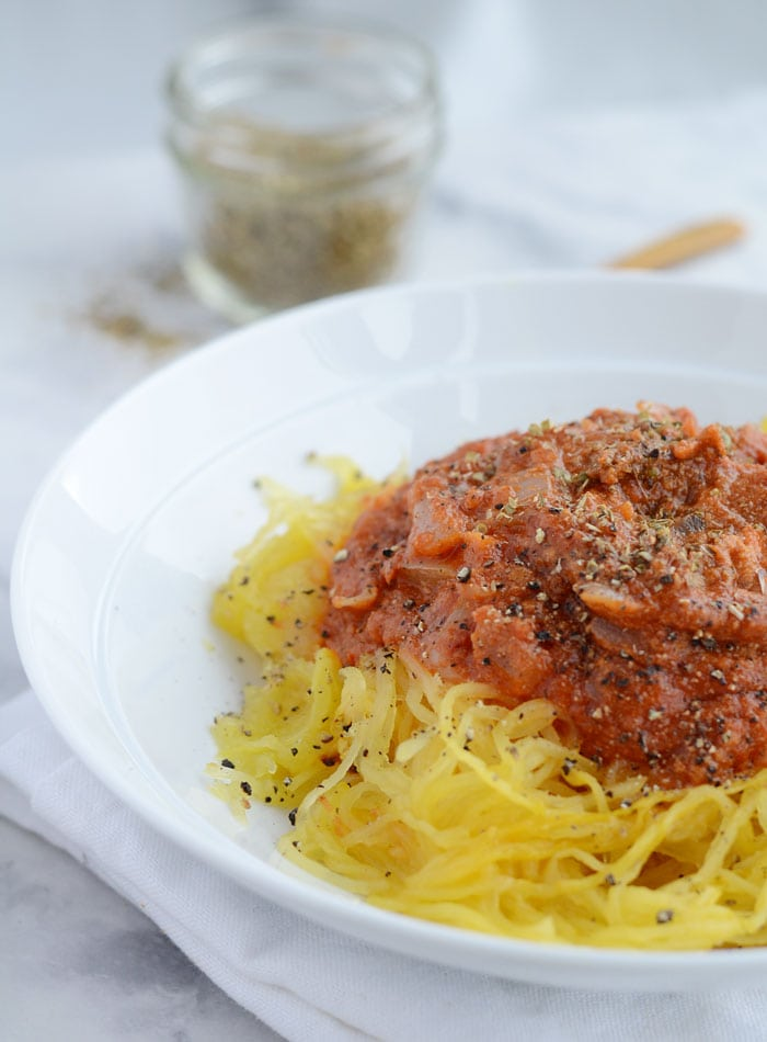 This cheesy vegan spaghetti squash marinara is low in calories, low in fat and carbs but packed with plenty of flavour! Easy to make with minimal ingredients: spaghetti squash, marinara sauce, onion, garlic and nutritional yeast. Healthy, quick & absolutely delicious!