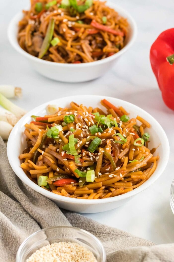 Bowl of vegan low mein noodles topped with green onion and sesame seeds.