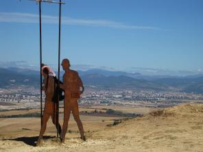 Peregrino sculptures with Pamplona in the distance.
