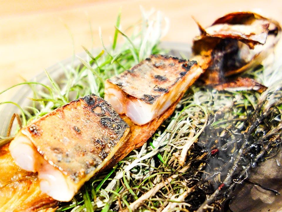 Chefkok Kobe Desramault van In de Wulf serveert makreel op een tak brandend kerrieblad