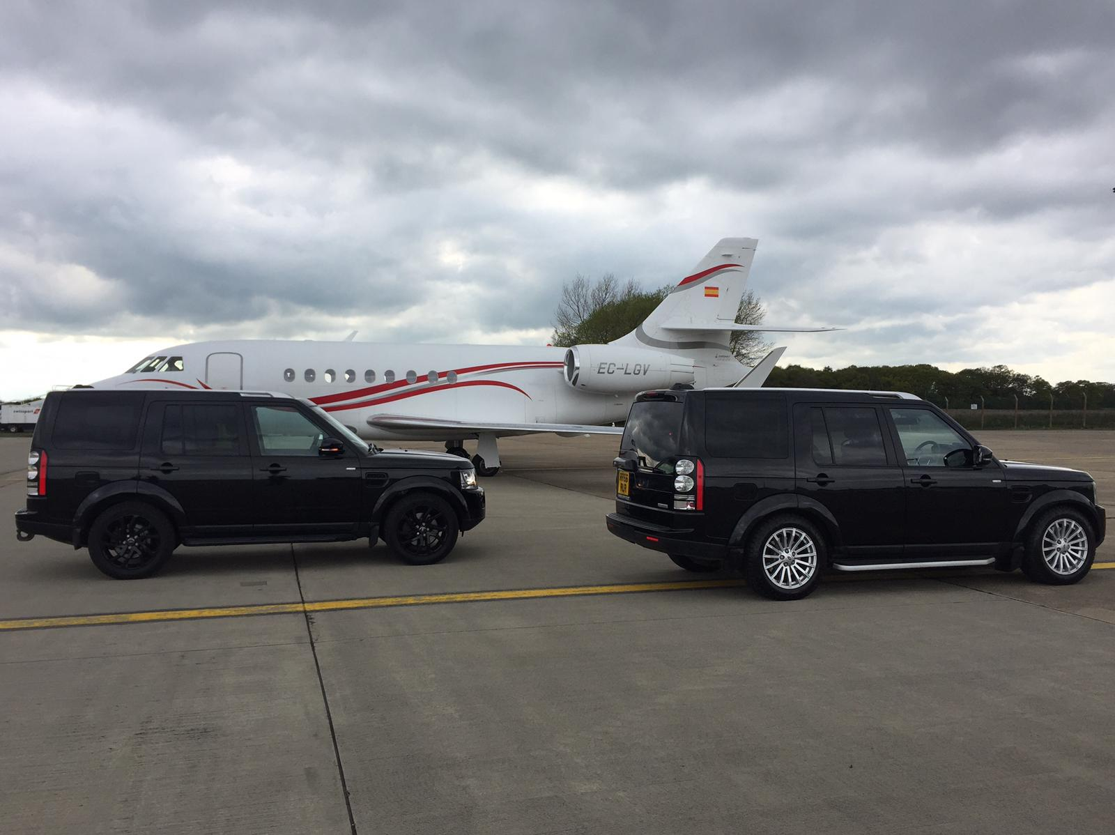 Two Landrover Discoveries next to Private Jet at Durham Airport