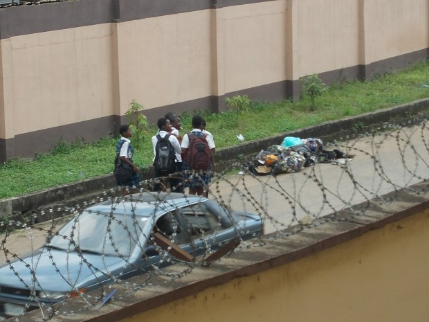 Lagos: Secondary students coming back from school. The street dump-site is a threat to children's health.