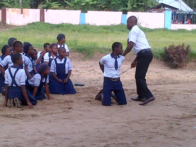 Students being chastised for not paying their school fees.