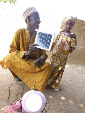 Umaru Kabiru and his granddaughter with the solar powered lamp by UNDP