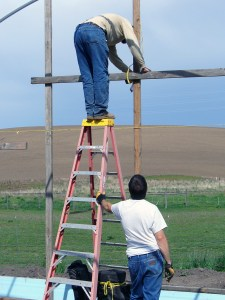A man holds a ladder for another person working.
