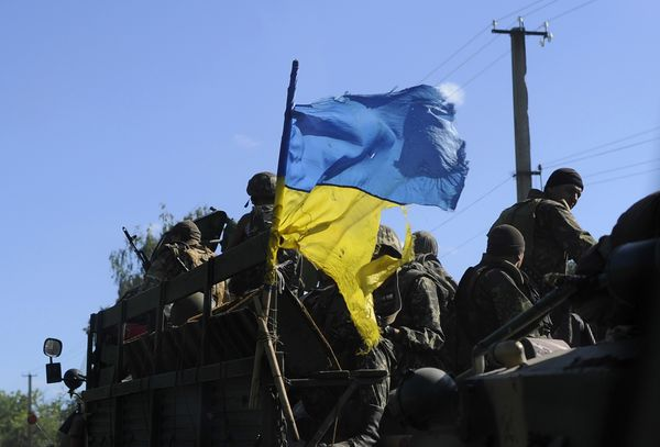 Ukrainian soldiers drive a military vehicle with a torn Ukrainian flag at a checkpoint near Slaviansk in eastern Ukraine