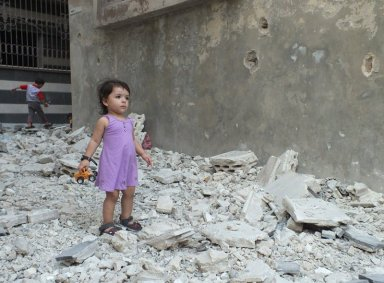 A girl stands on debris next to a damaged building at a besieged area of Homs, August 2, 2012. Picture taken August 2, 2012. REUTERS/Yazen Homsy  (SYRIA - Tags: POLITICS CIVIL UNREST)