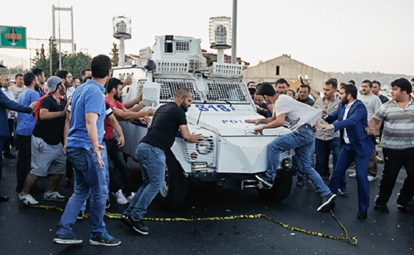 People attack and try to stop a Turkish police armored vehicle, carrying Turkish soldiers that participated in the coup and surrendered, backdropped by Istanbul's iconic Bosporus Bridge, Saturday, July 16, 2016.  Turkish President Recep Tayyip Erdogan told the nation Saturday that his government is in charge after a coup attempt brought a night of explosions, air battles and gunfire across the capital of Ankara. (AP Photo/Emrah Gurel)