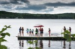 Camp North Woods campers jump off the dock Tuesday morning at the Maine 4-H Camp and Learning Center at Bryant Pond.