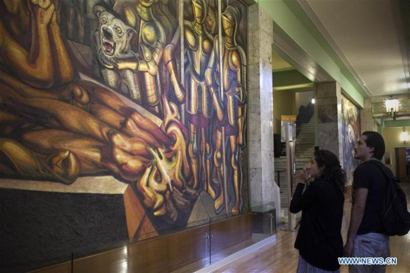 visitors watching a mural by David Alfaro Siqueiros in the Museum of Palacio de Bellas Artes in Mexico City, capital of Mexico.