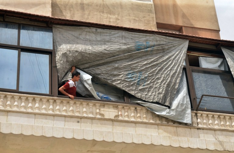 A man peers through a tarpaulin used to seal a broken window in a government-controlled district of the northern Syrian city of Aleppo on May 21, 2016.