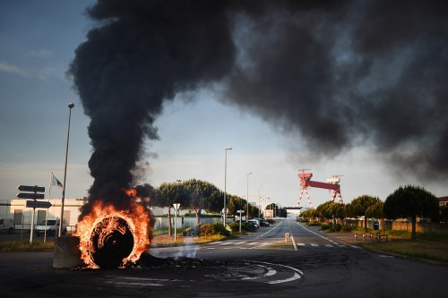Workers on strike set up a burning barricade to block access to the harbour of Saint-Nazaire, western France
